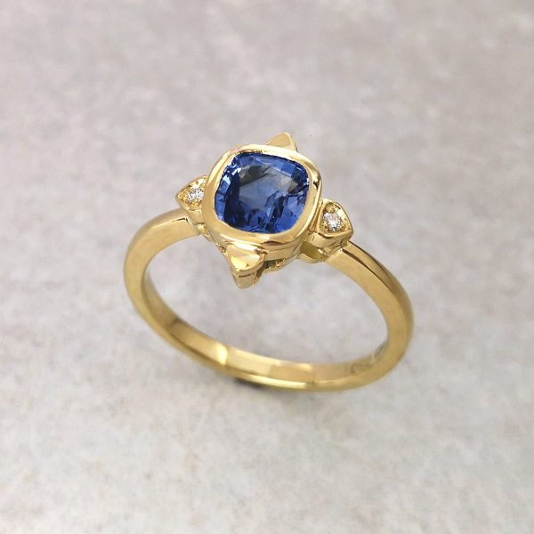 "18ct Gold Sapphire and Diamond ""Folia"" Ring -- A magnificent cushion-cut sapphire set in 18ct gold with two brilliant cut diamonds. Colour, form and craft meet to create this eye-catching beauty. Sapphire measures 5.8mm by 6.5mm. Finger size: O. Available with other gemstone and gold combinations, prices on request. David Wilson Jewellery Shop"