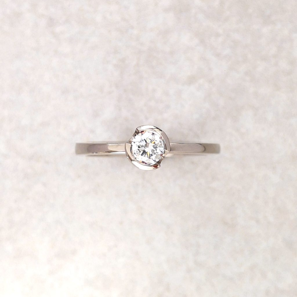 "18ct White Gold ""Solo"" Ring -- A vibrant, round brilliant cut diamond, half bezel set in white gold. Simply a beautiful, understated solitaire. Again, available in different size and shaped diamonds. Diamond measures 4mm diameter, .26carat diamond weight. Finger Size: K. David Wilson Jewellery Shop"