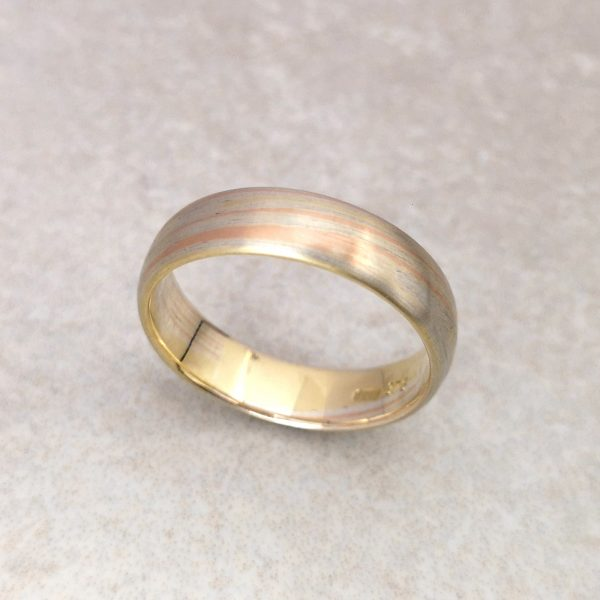 Mokume Gane Wedding Band -- Mokume Gane is a Japanese Metalwork Technique (loosely translated as wood grain) where layers and layers of (in this case) red, yellow and white gold are fused and forged to create an effect that is different everytime, but always unique and beautiful. Handmade by David Wilson. Can be made to different dimensions with different combinations of materials, please get in touch. This ring measures 5.3mm x 1.5 mm. Finger size: Q. David Wilson Jewellery Shop