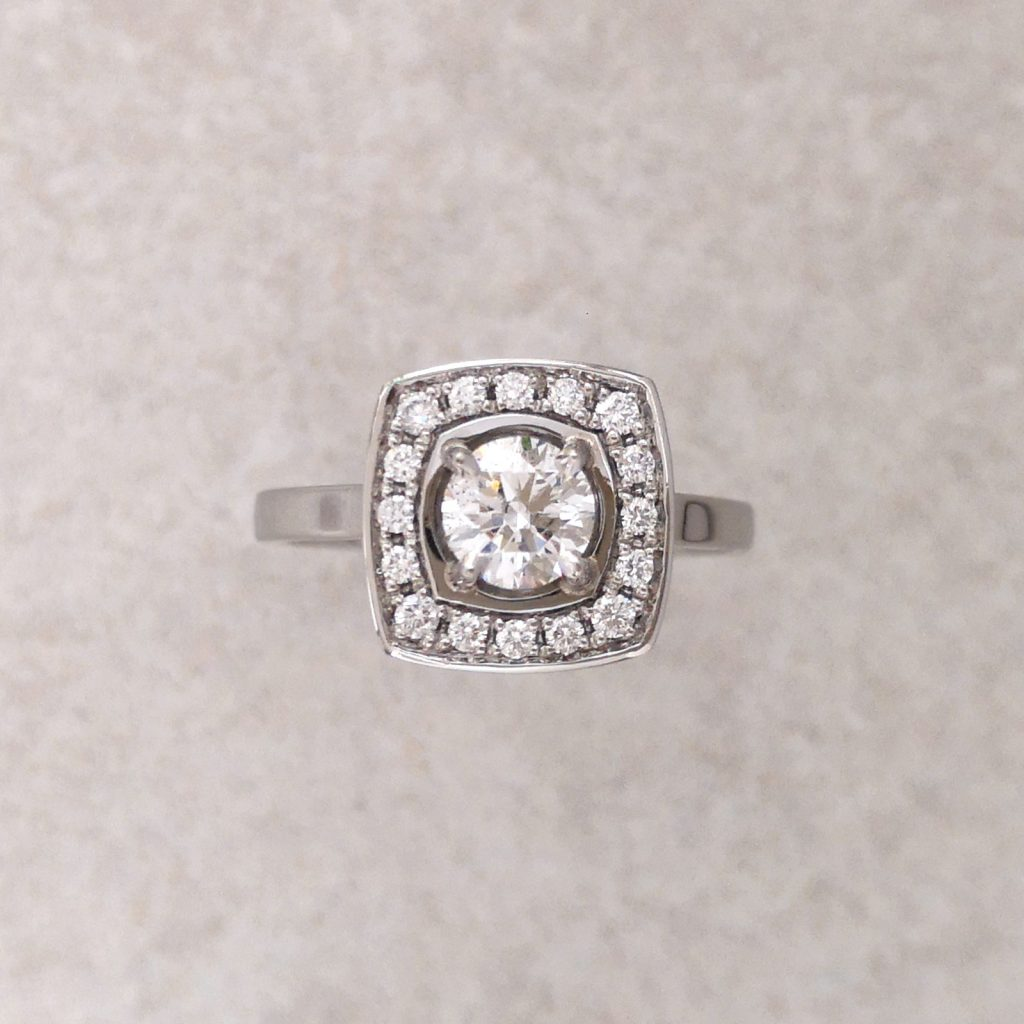 Diamond and Platinum Soft Square Halo Ring -- A magnificent diamond soft square engagement ring, completely made by hand in platinum. Featuring a centre diamond of over half a carat surrounded by 16 smaller brilliant cut diamonds. A special ring for a special time. Total halo width 10.6mm. Ring shank 2mm x 1.5mm. Centre diamond .52ct (5.15mm diameter) F colour SI2, excellent cut, GIA cert. Total diamond weight in ring: .68ct. Finger Size: M ½. David Wilson Jewellery Shop