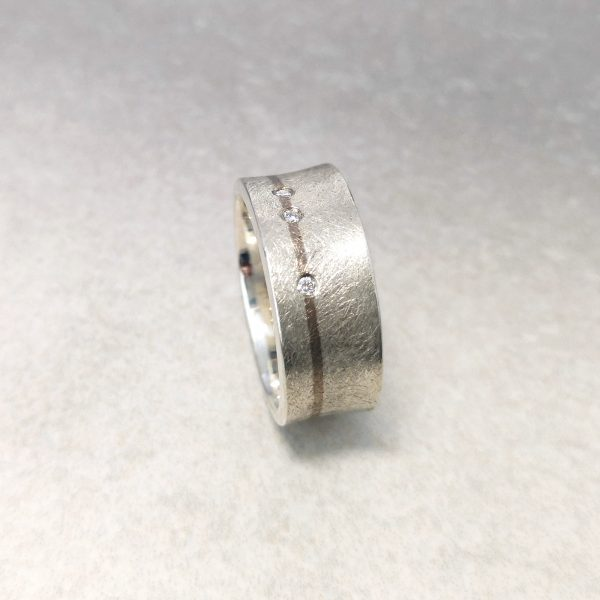 "Gents ""Equipoise"" Ring -- Sterling silver, 18ct white gold and three round brilliant cut diamonds make up this bold contemporary band. The contrast in finish and colour and the comfort despite the generous dimensions, make this a striking ring. Ring measures 9.4mm by 1.8mm. Finger size: T ½. David Wilson Jewellery Shop"