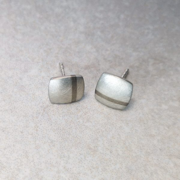 Silver and White Gold Stripe Ear Studs -- A silver soft square with a bold 18ct white gold stripe. The brushed finish highlights the contrast of these precious metals and makes for a playful and interesting ear stud. Handmade. Ear studs measure 8mm x 8mm and are supplied with large earring backs for extra comfort and security. David Wilson Jewellery Shop