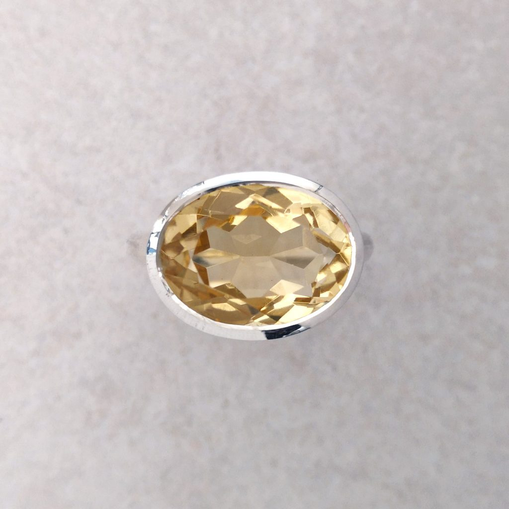 Silver Oval Citrine Ring -- A beautiful pale citrine set in a tapered bezel sits across the finger on a totally round band. Citrine measures 12mm X 16mm. Band measures 3mm diameter. Finger size: L. David Wilson Jewellery Shop